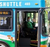 Masked village shuttle driver waving